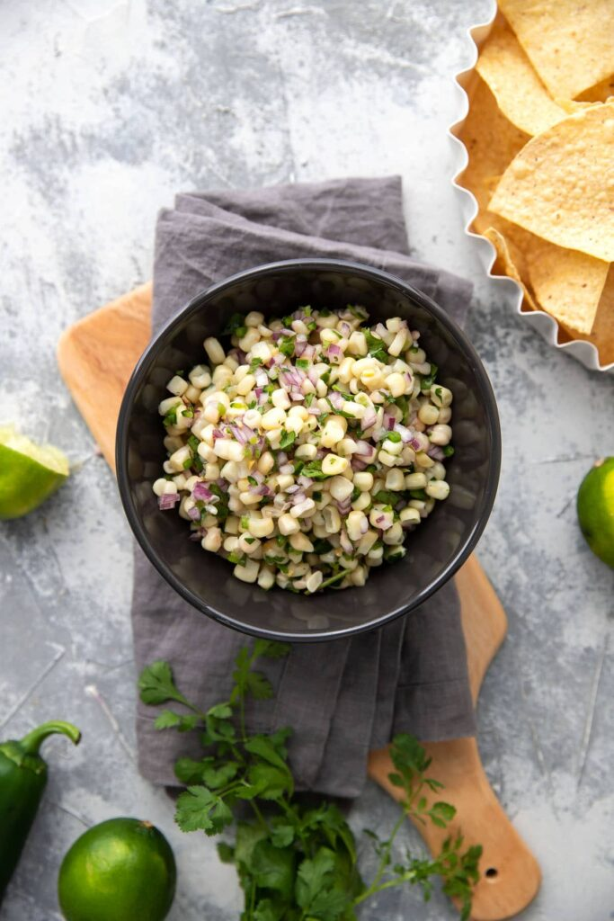 white corn salsa with red onions and peppers in a grey bowl