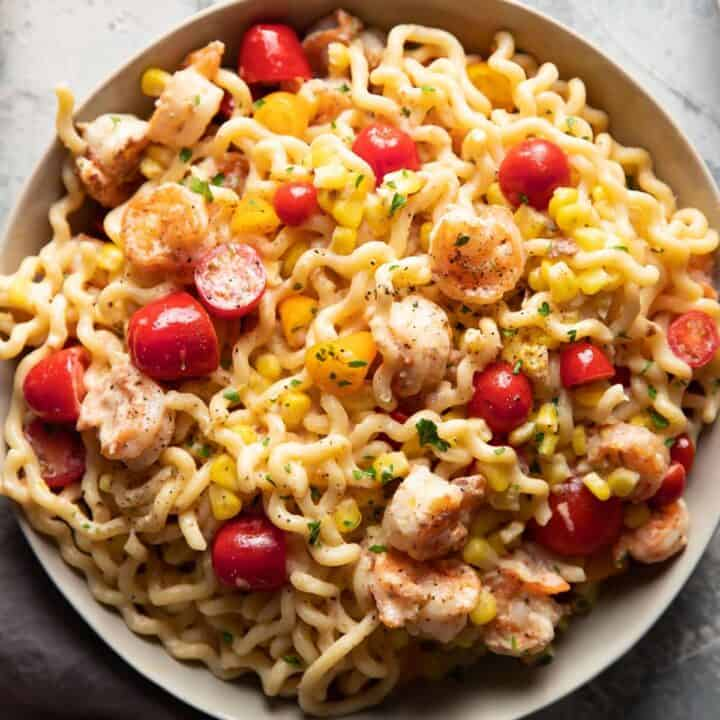 fusili pasta with shrimp corn and tomatoes in a bowl