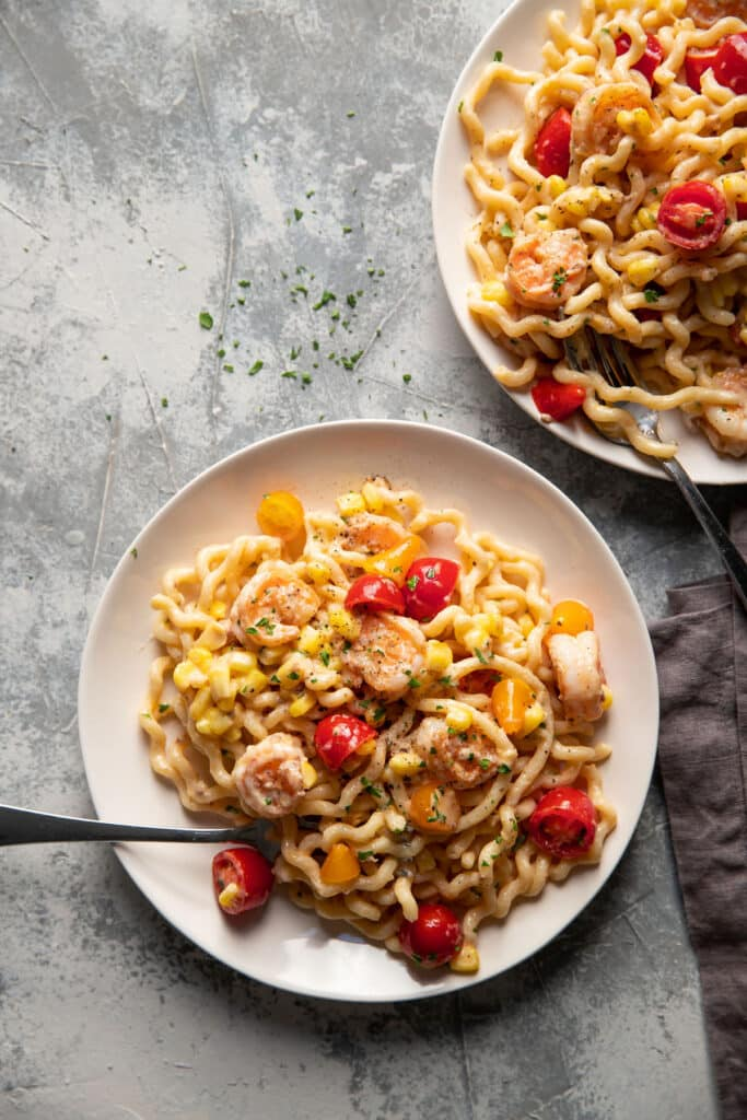 fusili pasta with shrimp corn and tomatoes on a plate