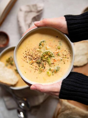 hands holding a bowl of broccoli cheese soup