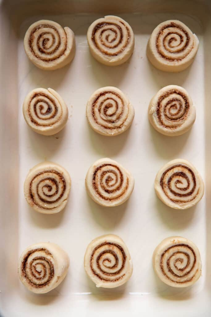 cinnamon roll pieces in a baking pan before baking