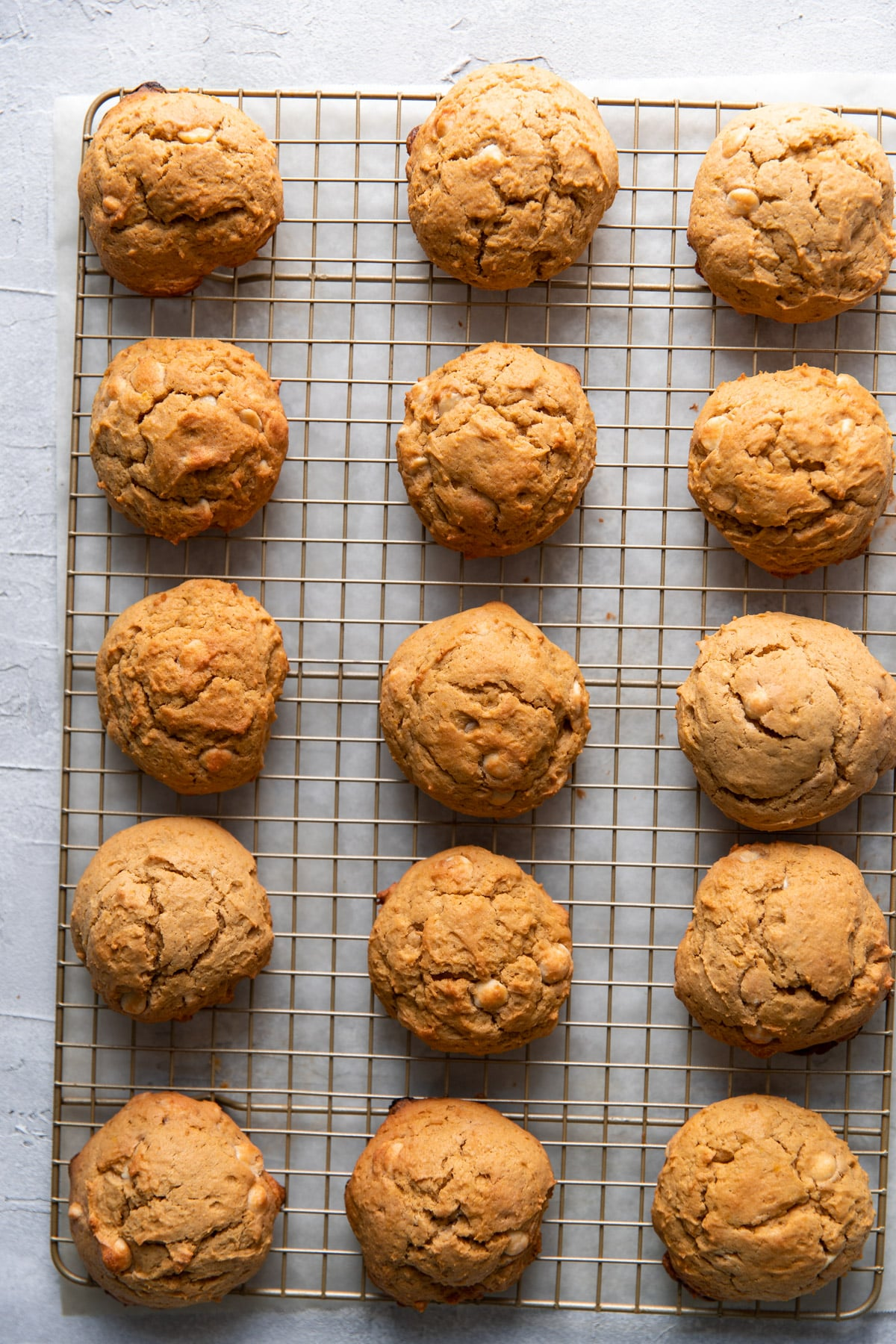 pumpkin cheesecake white chocolate chip cookies on a wire rack