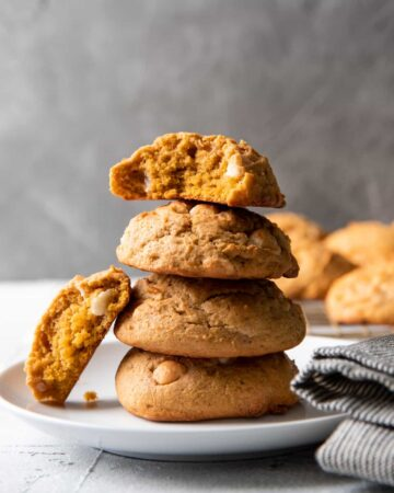 pumpkin cookies stacked on a plate