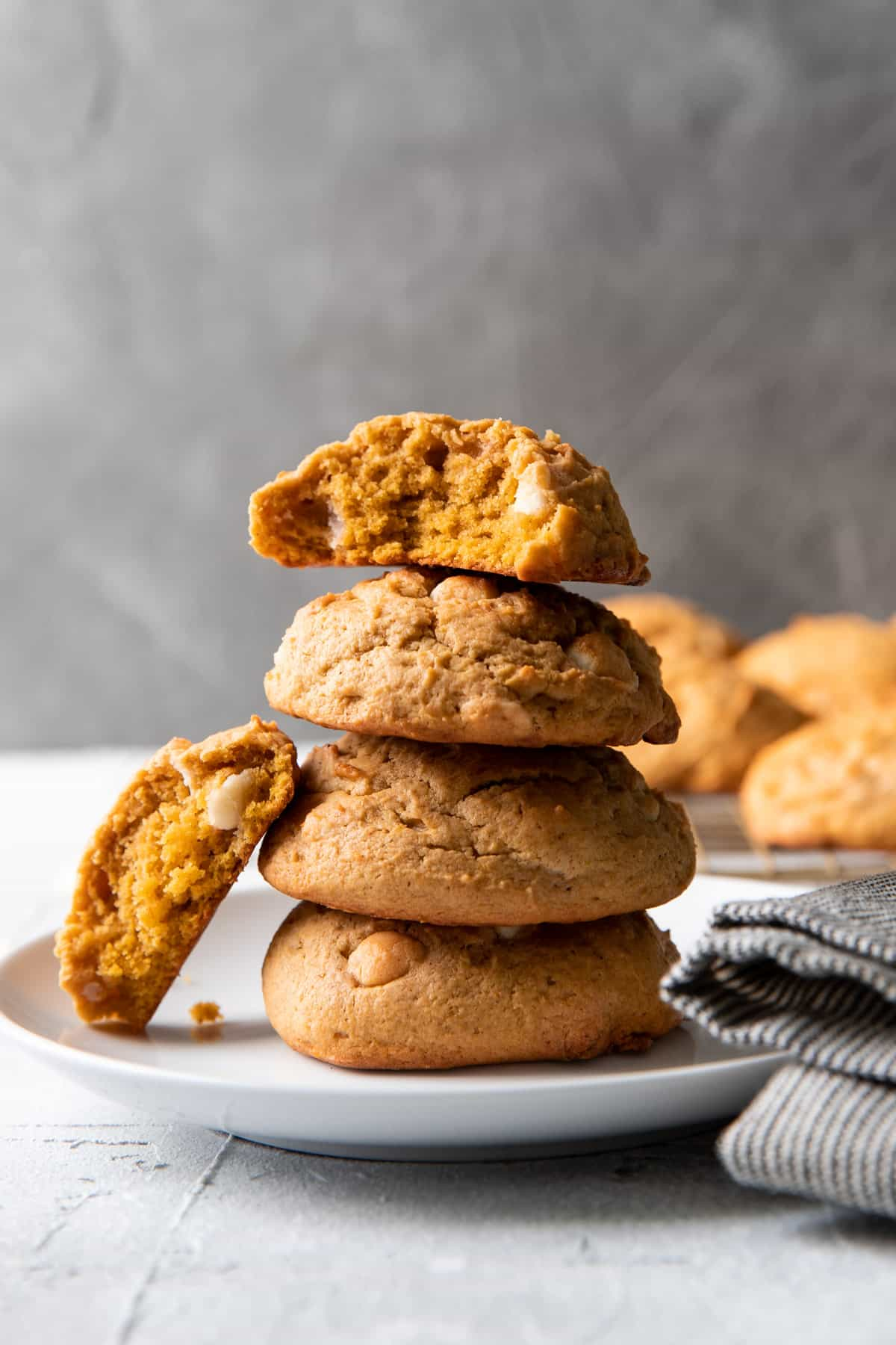 pumpkin cheesecake white chocolate chip cookies stacked on top of each other