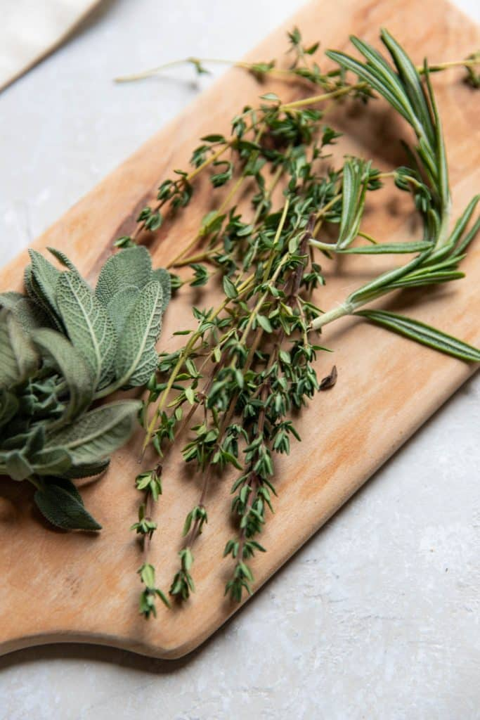 rosemary sage and thyme on a wooden cutting board