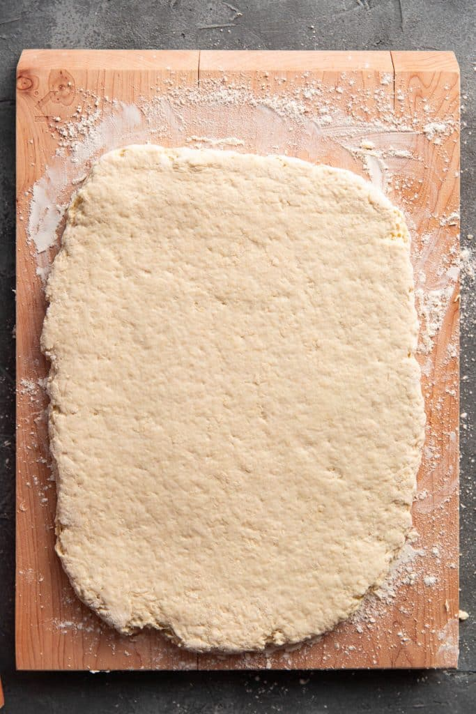 biscuit dough on a cutting board rolled out