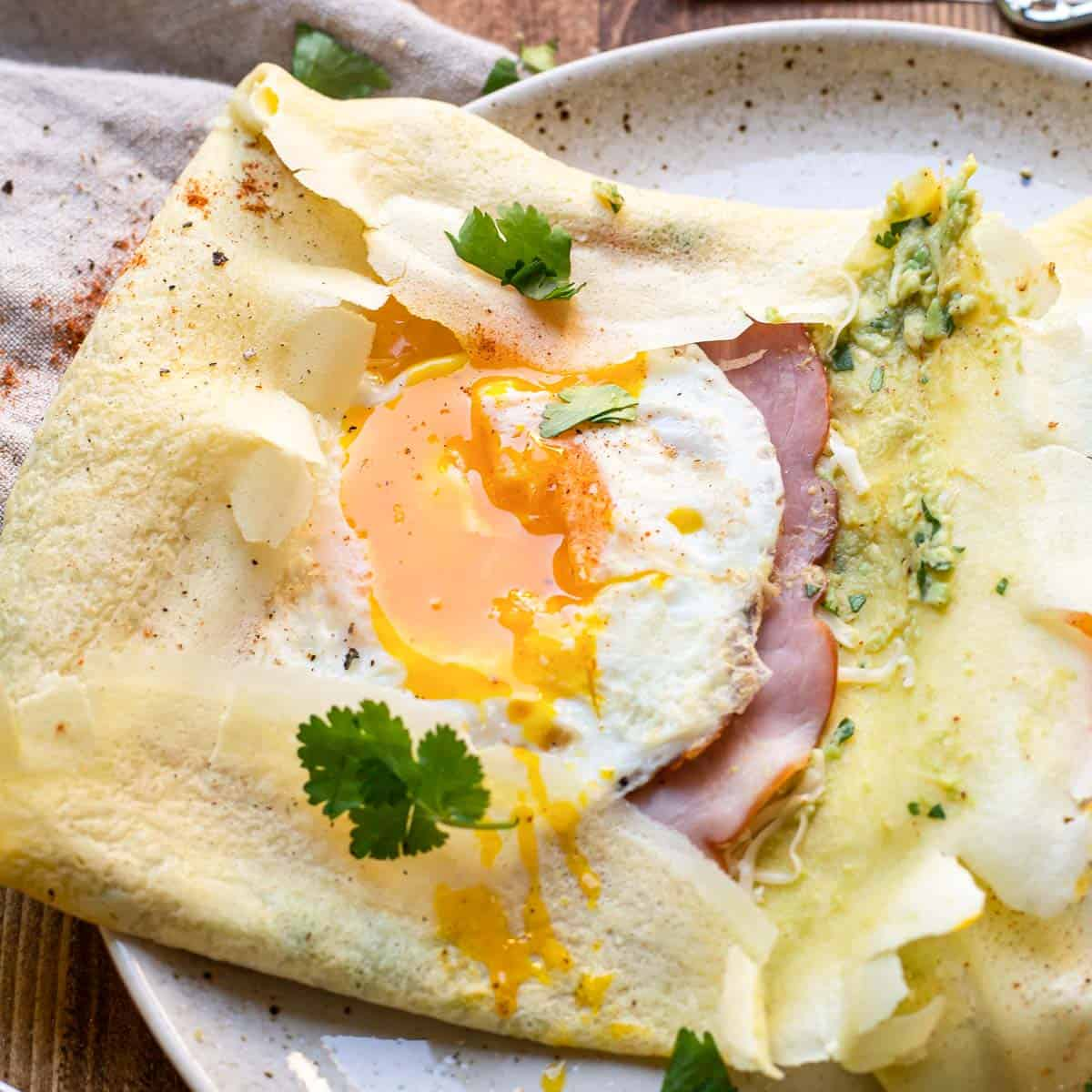 savory crepe with guacamole, jack cheese, ham and a sunny side up egg.