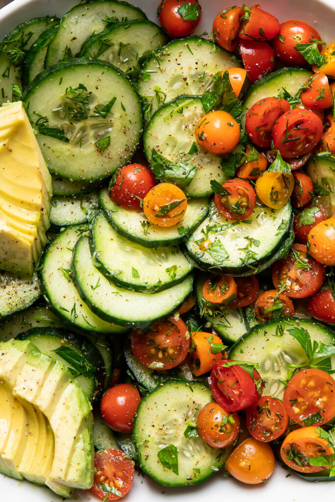 Up close image of a cucumber avocado salad with tomatoes.