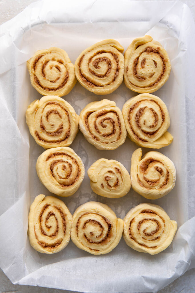 Orange rolls in a baking pan before cooking.