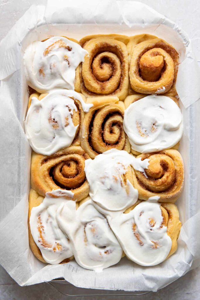 Orange rolls in a baking pan after cooking.
