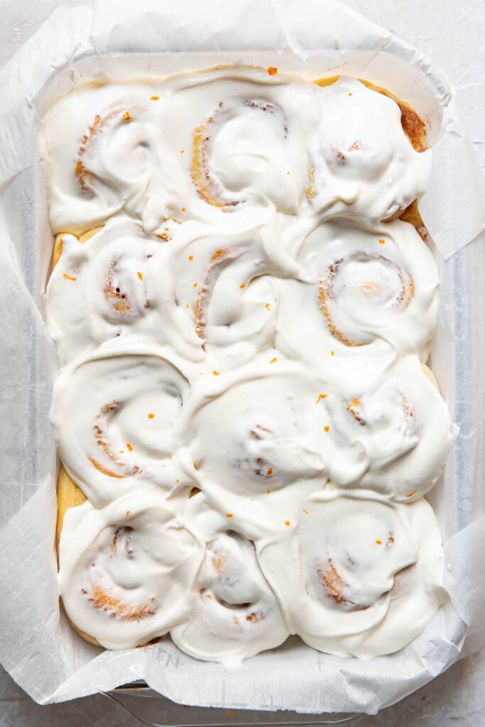 Orange rolls with cream cheese frosting on top.