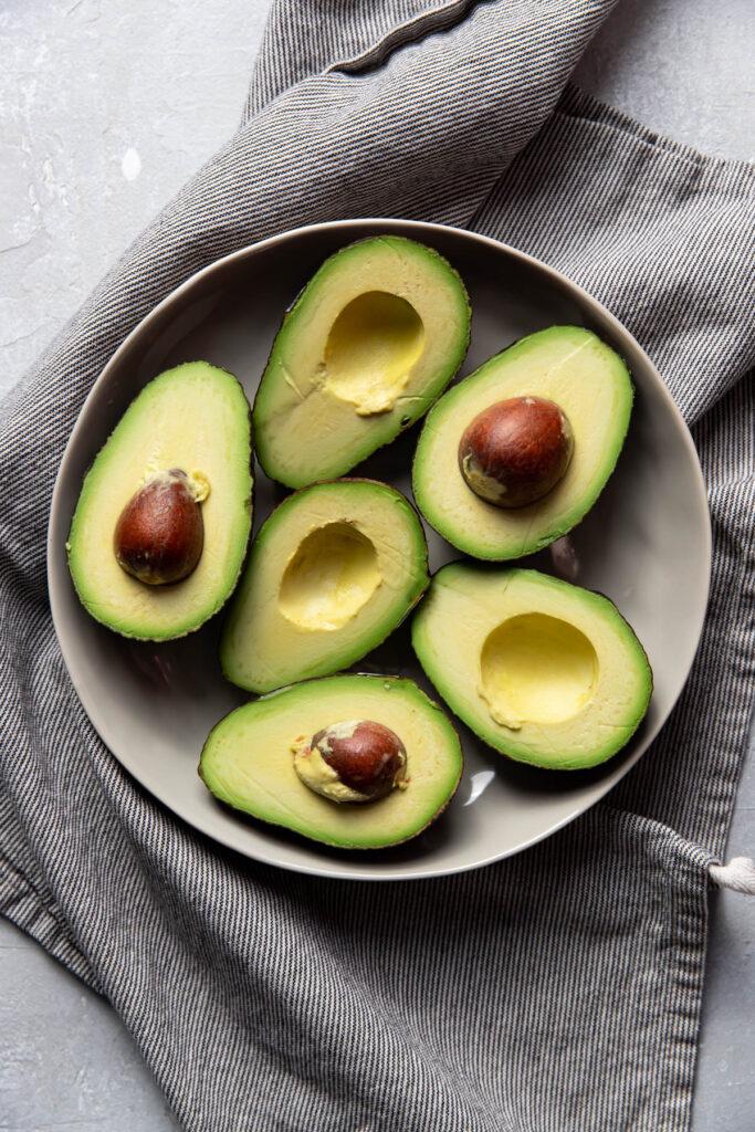 avocados cut in half in a bowl.