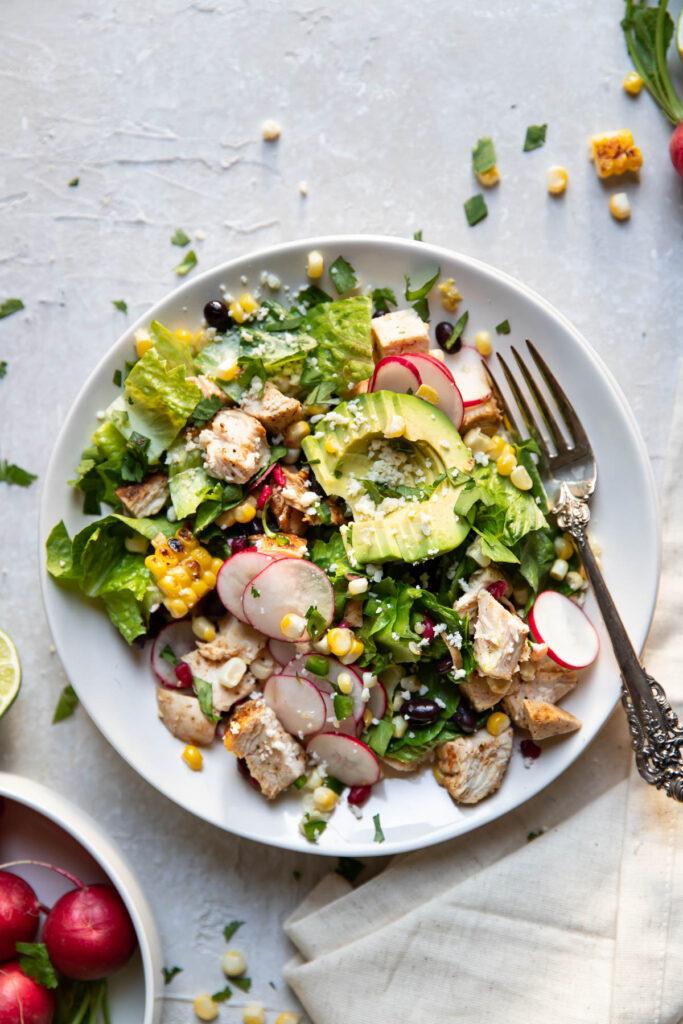 avocado pomegranate chicken salad on a plate.