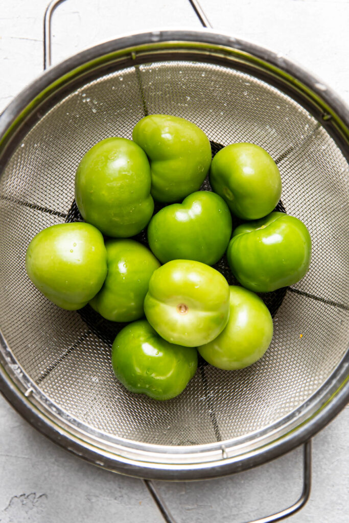 clean tomatillos in a collander.
