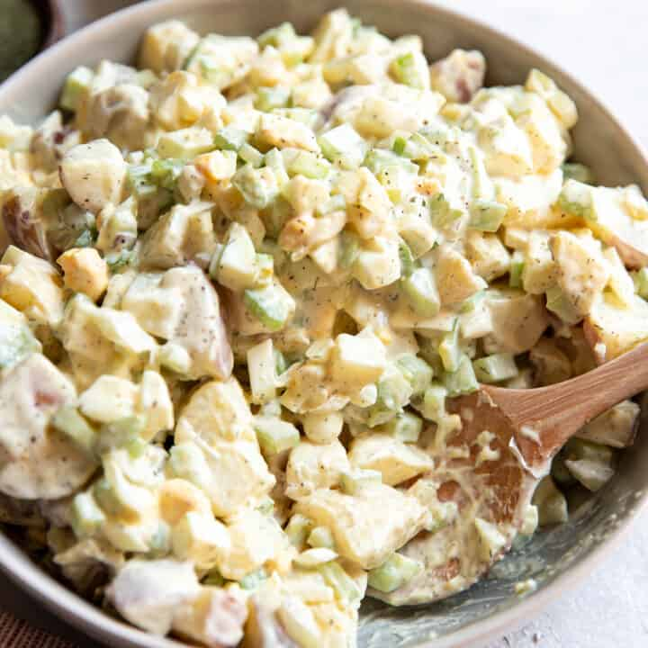 red potato salad with egg cucumber and celery in a bowl.
