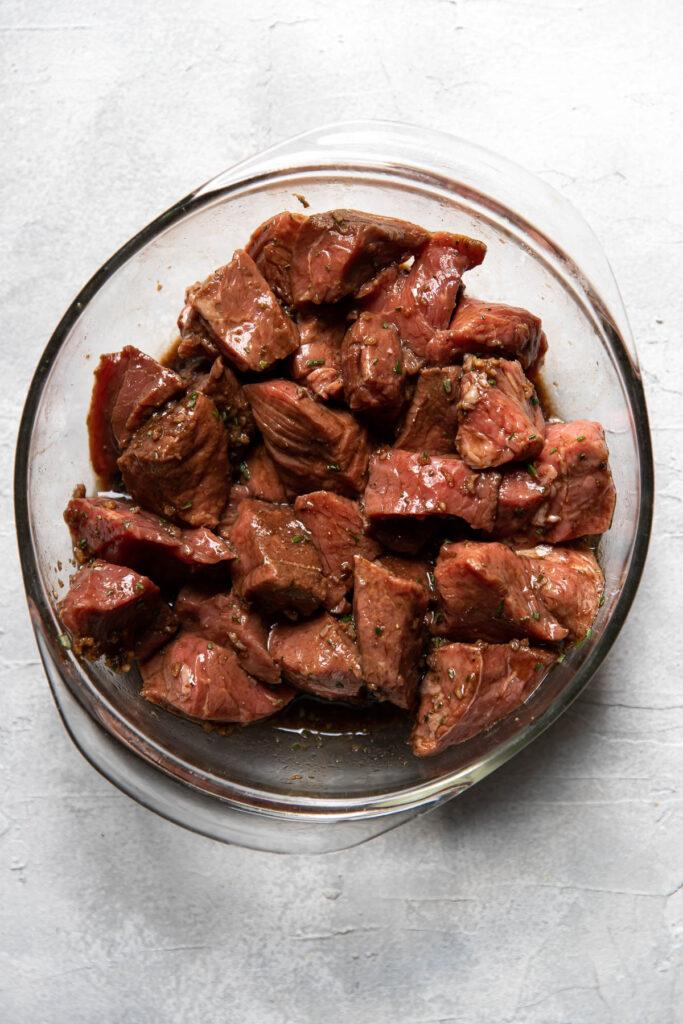 steak marinating in a bowl.
