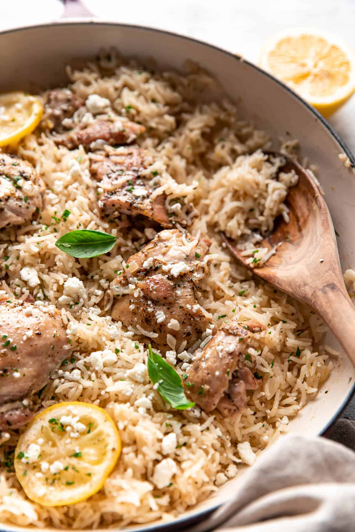 greek chicken and rice with lemon slices and feta in a pan.