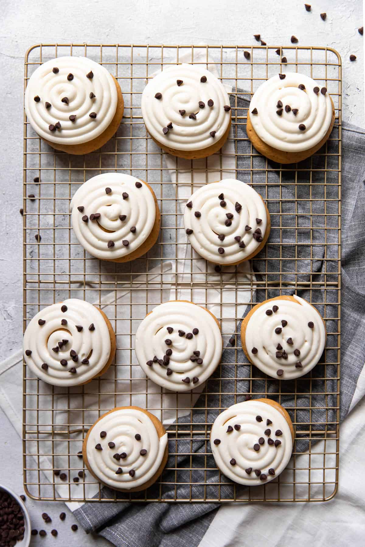 pumpkin cake cookie with cream cheese frosting and chocolate chips on top.