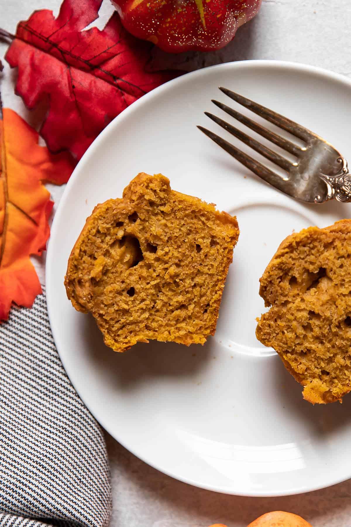 pumpkin muffin cut in half on a plate.