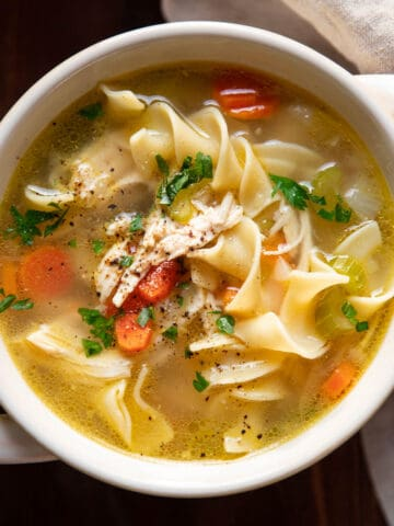 bowl of chicken noodle soup with egg noodles.